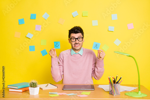 Photo of young unhappy upset worried sad man in glasses showing happy and sad paper emoji isolated on yellow color background