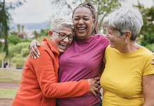 Happy Multiracial Senior Women Having Fun Together At Park - Elderly Generation People Hugging Each Other Outdoor