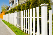 A White Fence In Front Of A House.