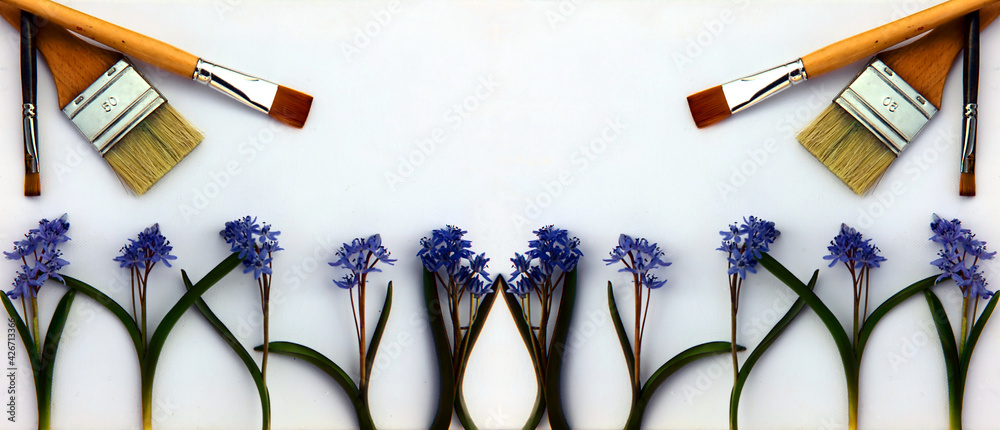 Fototapeta A creative arrangement made of blue flowers and paint brushes on a white background. Paint brushes and wild blue flowers, top view, place for text. Art spring flowers background.