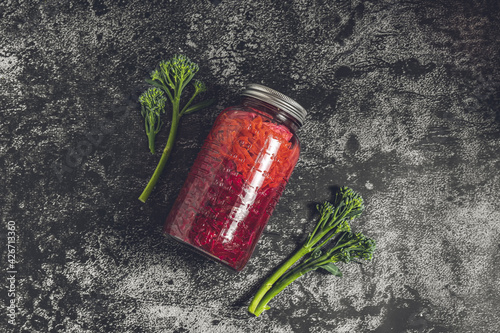 Foto Flat lay dark moody food photography of a jar with homemade fermented red cabbage chucrut