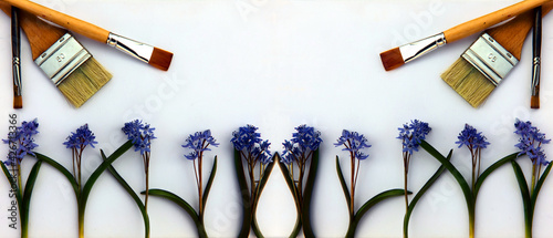 Fototapeta A creative arrangement made of blue flowers and paint brushes on a white background. Paint brushes and wild blue flowers, top view, place for text. Art spring flowers background. obraz