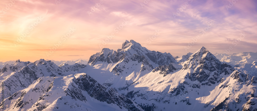 Fototapeta Aerial View from Airplane of Blue Snow Covered Canadian Mountain Landscape in Winter. Colorful Pink Sky Art Render. Tantalus Range near Squamish, North of Vancouver, British Columbia, Canada.
