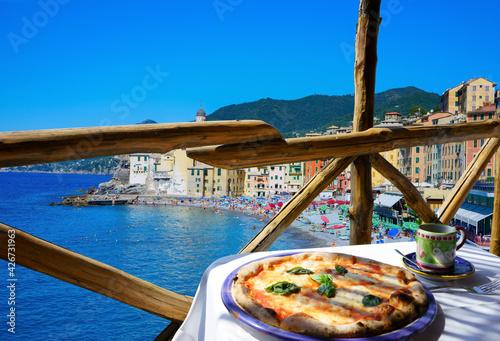 Fotografie, Obraz Pizza place terrace overlooking to beautiful Camogli harbor, Italian Riviera, Liguria