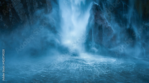Obraz Stirling Falls plunging vertically over the cliff into Milford Sound, fanning out at its base in circular ripples on the surface of the water, New Zealand - fototapety do salonu
