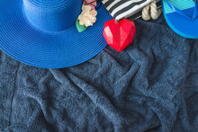 Summe Beach Holidays Concept. Blue Women's Beach Hat, Red Heart, Flip Flop And Beach Bag On Dark Blue Towel Top View; Space For Text