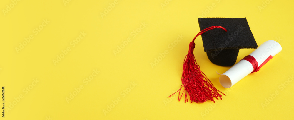Fototapeta Academic hat with diploma on yellow background. Graduation theme
