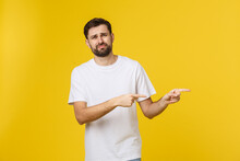 Handsome Man Over Isolated Yellow Wall Frustrated And Pointing To The Front.