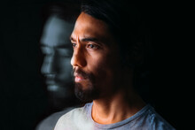 Close-up Of The Face Of A Latin Man And Next To Him His Own Depressed Portrait With Closed Eyes. Long Exposure Image On Black Background. Depression Concept