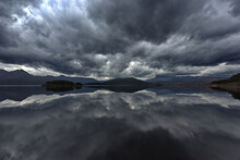 Rolling Storm Clouds And West Coast Range Mountains Reflect In Lake Burbury In Tasmania, Australia