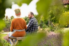 Happy Couple Taking A Break From Gardening In Backyard