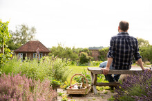 Man Taking A Break From Gardening In Idyllic Sunny Cottage Garden