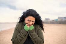 Happy Woman In Winter Coat On Beach
