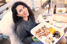 Portrait Happy Woman With Fresh Seafood At Patio Table