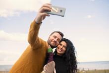 Happy Couple Taking Selfie On Ocean Beach