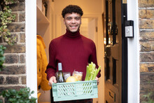 Portrait Happy Young Man Receiving Grocery Delivery At Front Door