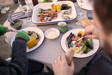 Couple Enjoying Fresh Seafood On Patio Table