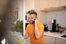 Happy Young Man Working From Home Talking On Smart Phone At Laptop