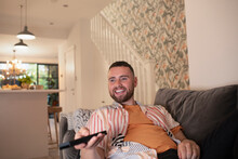 Happy Young Man With Remote Control Watching TV On Sofa