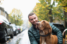 Happy Young Man With Dog On Wet Urban Street