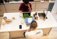 Young Gay Male Couple Working From Home At Laptops In Kitchen