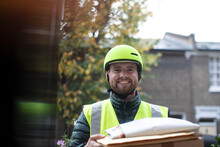 Portrait Friendly Delivery Man In Helmet Delivering Packages At Door