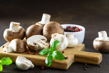 Fresh Raw Champignons With Aromatic Basil Leaves And Peppercorn On The Cutting Board On Dark Rustic Background.