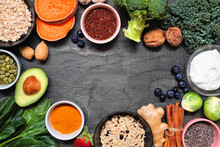 Set Of Healthy Food Ingredients. Top View Top Frame On A Slate Background. Copy Space. Super Food Concept With Green Vegetables, Berries, Whole Grains, Seeds, Spices And Nutritious Items.