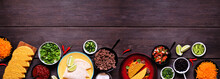Taco Bar Bottom Border With Assorted Ingredients. Top View On A Dark Wood Banner Background. Mexican Food Buffet. Copy Space.