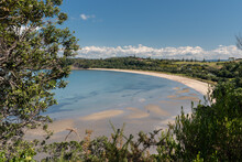 Elevated View Of The Sandy Beach At Te Haruhi Bay At Shakespear Regional Park, Whangaparaoa, Auckland, New Zealand, On A Sunny Day.