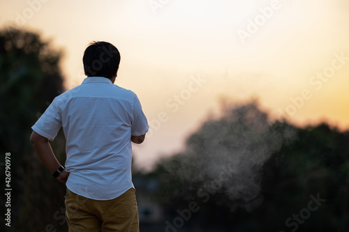 Fotomural Asian man is smoking backside in the twilight time.