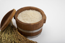 Rice In A Wooden Bucket And A Ear Of Paddy On White Background