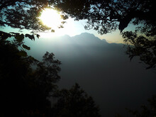 The Sun Rises Behind The Lush Mountain Forest