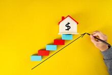 Businessman Drawing An Arrow Up Above The Houses. The Concept Of Growth In Demand For Real Estate. Increase In The Value Of Property,