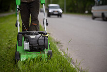 A Front View Of A Worker In Protective Clothing Walks Alongside The Road And Mows The Grass With A Wheeled Lawnmower.A Man Mows The Grass On The Side Of The Road Against The Background Of Passing Cars