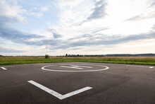 A Large Area With A Special Symbol In The Center For Helicopter Landing. Private Helipad In A Green Field Against The Backdrop Of Evening Clouds.