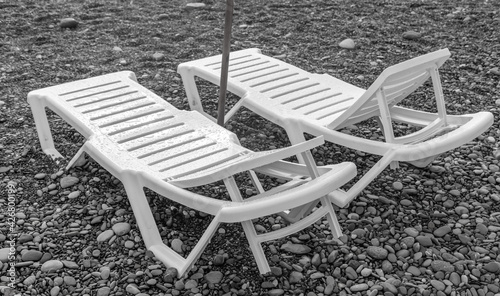 Obraz na plátne Sun loungers on a pebble beach