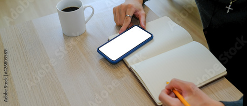 Obraz Cropped shot of man writing on empty notebook and using smart phone at home office. - fototapety do salonu
