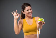 Approval Of A Healthy Sports Life. A Woman In Sportswear Holds An Apple Wrapped With A Measuring Tape, While The Other Hand Shows Approval. Nutrition Diet And Happy Fitness Lifestyle