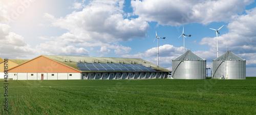 Fotografía Modern dairy farm using renewable energy, solar panels and wind turbines