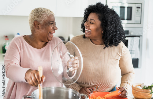 Fototapeta Happy Afro mother and daughter preparing lunch together in modern house kitchen
