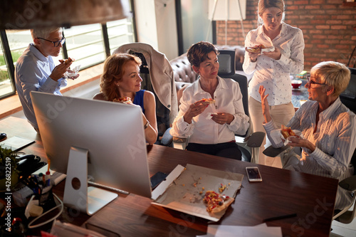 Obraz Group of cheerful business women are chatting while they eating a pizza at the break from work at workplace. Business, office, job - fototapety do salonu