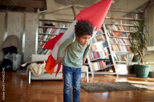 Obraz na plátně Cute afro american boy playing with paper rocket