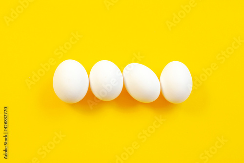 Fotografija White eggs on a yellow background in the center, top view, copy space