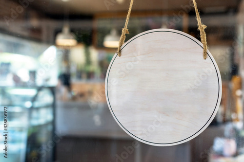 blank vintage wooden sign board hanging on glass door in modern cafe restaurant, Fototapete