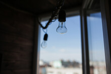 A Switched Off Light Bulb Hanging From The Ceiling.