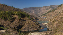 View Of A River Flowing Through A Narrow Valley With Rocky Mountains On The Sides And A Bridge On Top Of It In The Kumaun Region Of UttaraKhand India On 12 January 2021