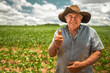 Leinwandbild Motiv Farmer working on soybean plantation. Elderly man looking at camera with thumbs up