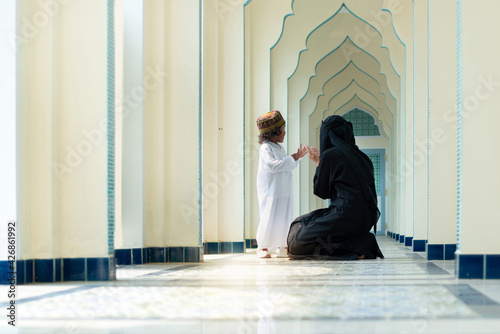 Leinwand Poster Muslim mother teach her son praying, relationship between Muslim mother and chil