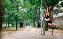 Female Athlete Doing Monkey Exercises On Rings In A Park